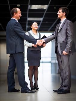 Uomini d'affari allegri che si stringono la mano