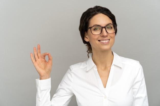 Donna d'affari allegra indossare camicetta di buon umore sorridente ampiamente, mostrando il gesto giusto in studio.