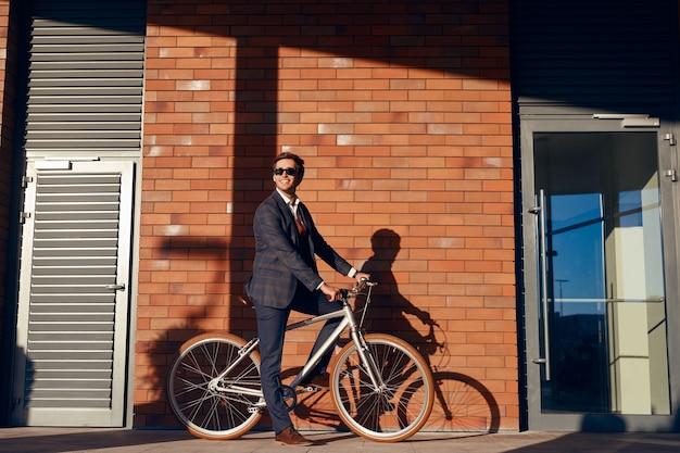 Allegro uomo d'affari in bicicletta su strada