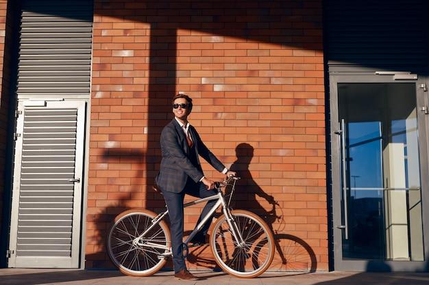 Allegro uomo d'affari in sella a bici su strada