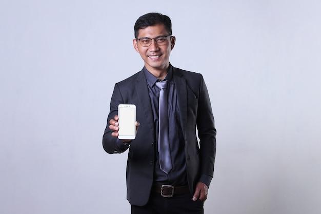 Uomo d'affari allegro che mostra telefono cellulare con schermo vuoto