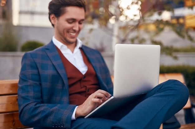 Allegro uomo d'affari utilizzando laptop sulla strada