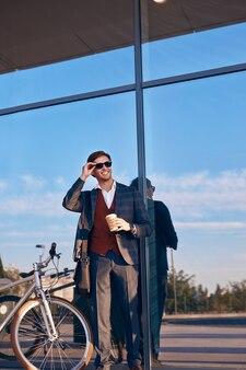 Allegro uomo d'affari con bicicletta e caffè in piedi sulla strada