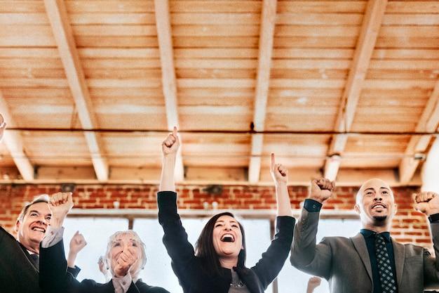Uomini d'affari allegri che alzano le mani in aria
