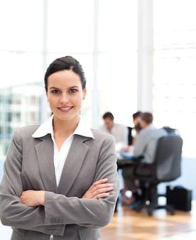 Donna di affari allegra che sta davanti alla sua squadra mentre lavorando