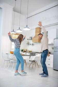 Padre allegro e spensierato con la figlia che balla a casa in cucina.