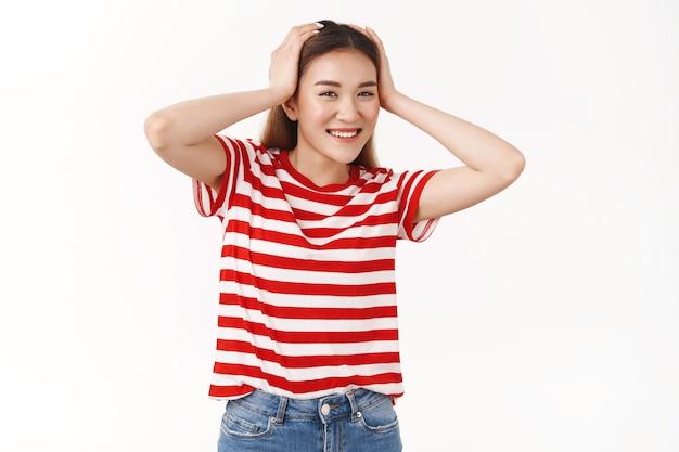 Allegra spensierata ottimista ragazza bionda asiatica che si gode le vacanze estive divertendosi toccando i capelli sognando nuotare in piscina arrivare all'hotel camminando sotto i piedi soleggiati sorridendo felice del muro bianco