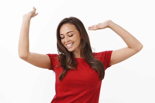 Allegra spensierata giovane donna divertirsi, ballare con le mani alzate in aria, godersi il concerto, chiudere gli occhi e sorridere a trentadue denti dalla felicità e dalla gioia