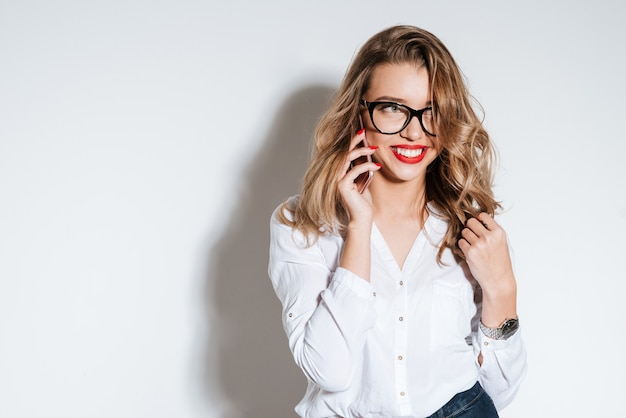 Donna casual allegra in occhiali che parla al telefono isolato su un muro bianco