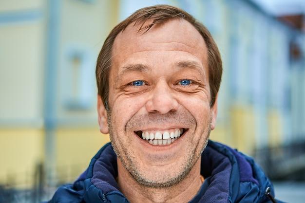 Allegro caucasico uomo di mezza età sorridente viso con la barba lunga con denti bianchi e occhi azzurri