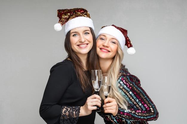 Allegre sorelle caucasiche beve champagne e si rallegrano, immagine isolata sul muro bianco
