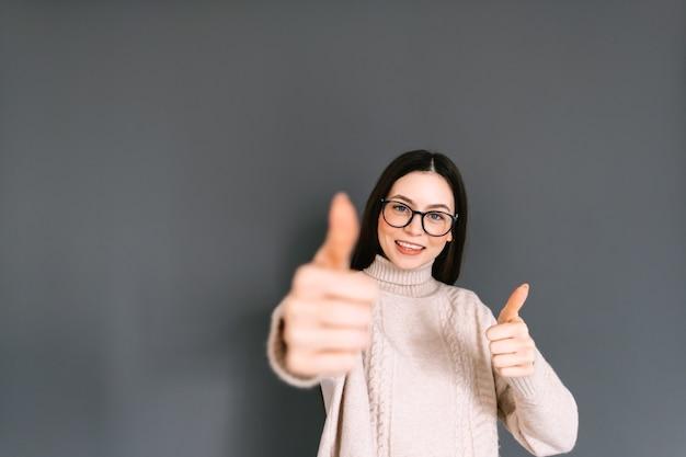 Allegra donna caucasica in occhiali che mostra i pollici in su