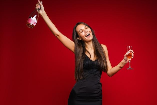 Allegra donna caucasica con un aspetto attraente con una bottiglia di champagne e vetro, immagine isolata su sfondo rosso