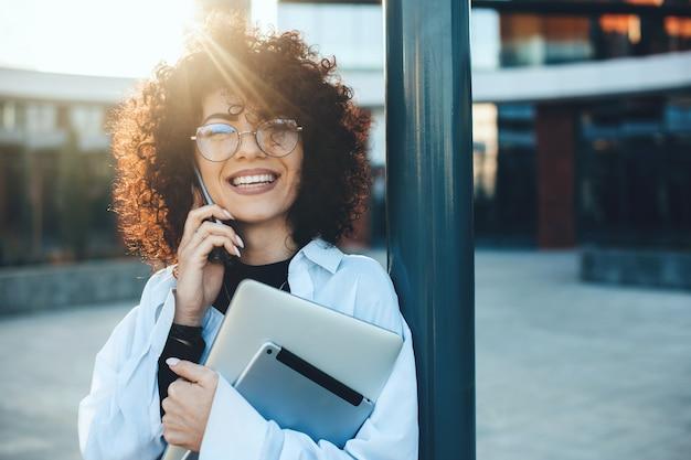 Donna caucasica allegra con capelli ricci che ha una discussione telefonica mentre posa con un laptop e un tablet all'esterno