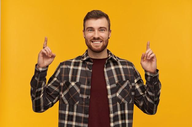 Allegro affascinante giovane uomo in camicia a scacchi con la barba in piedi e rivolto verso il cielo con due dita sul muro giallo