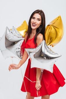 Allegra affascinante giovane donna in abito rosso che tiene palloncini a forma di stella e si diverte su sfondo bianco