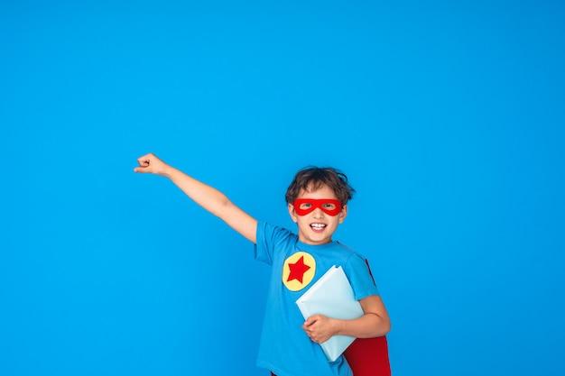 Il bambino allegro vestito in costume da supereroe tiene il libro e allunga la mano