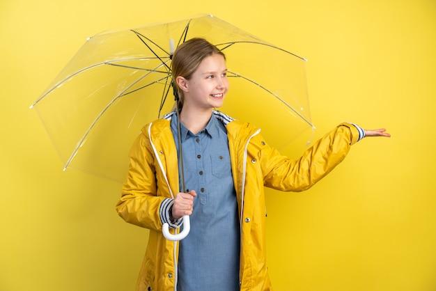 Ragazza allegra del bambino con l'ombrello e il cappotto di pioggia giallo sulla parete gialla