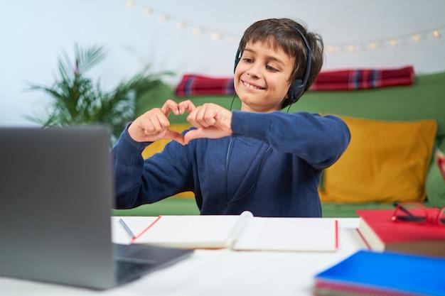 Bambino allegro che ha videoconferenza sul portatile a casa, indossa le cuffie e fa un cuore con le mani, spazio libero