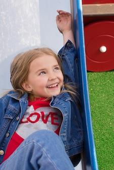 Un bambino allegro sta giocando nel parco giochi per bambini