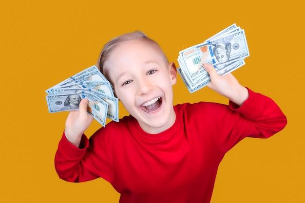 Un bambino allegro in rosso tiene un mucchio di banconote da un dollaro davanti alla sua faccia Foto Premium