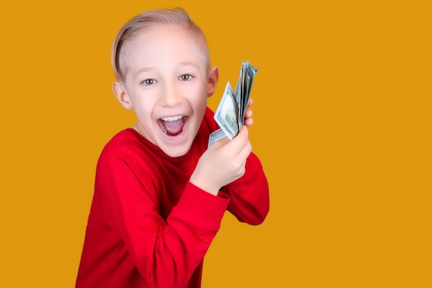 Un bambino allegro in rosso tiene davanti a sé un fascio di banconote e fa facce buffe Foto Premium