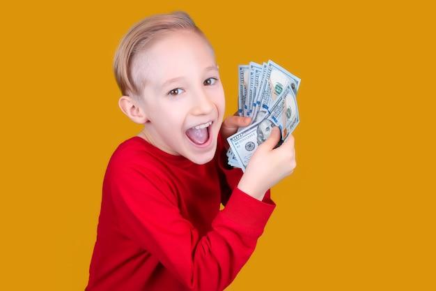 Un bambino allegro in rosso tiene davanti a sé un fascio di banconote e fa facce buffe