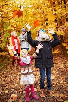 Bambini allegri che catturano foglie autunnali