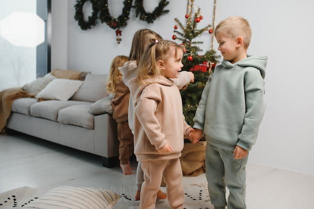 Bambini allegri con regali il prossimo albero di natale