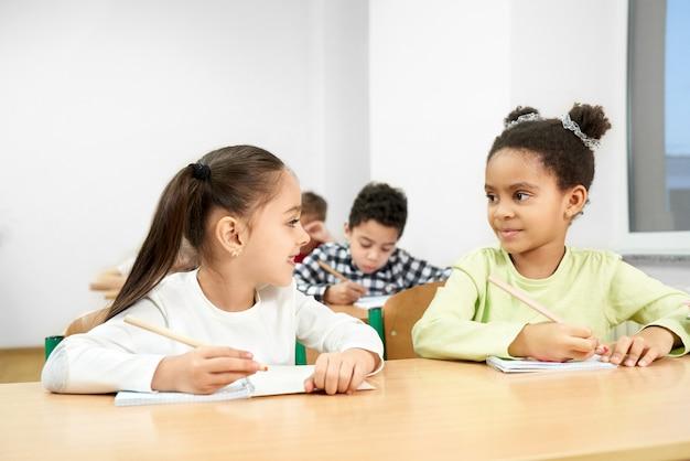 Compagni di classe allegri che si siedono alla tavola in aula alla scuola