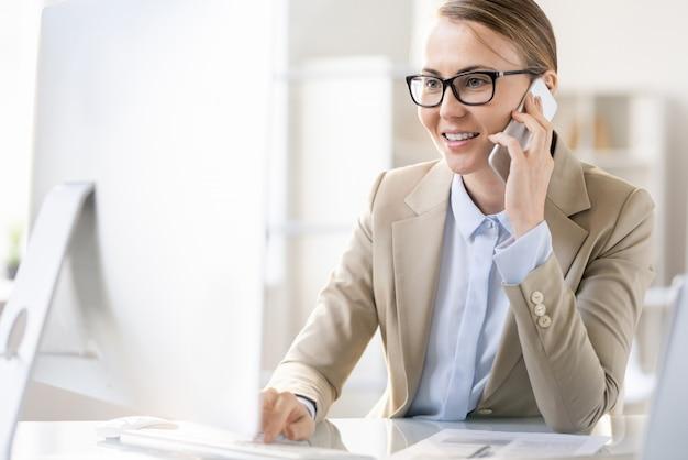 Allegro fiducioso giovane donna con gli occhiali seduto al tavolo e rispondere alla chiamata mentre si utilizza il computer in un ufficio moderno