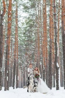 Le coppie allegre stanno giocando con il husky siberiano in foresta nevosa. matrimonio invernale.