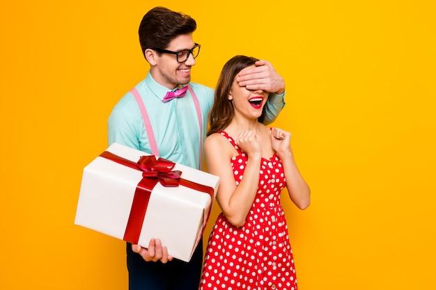 Il ragazzo allegro delle coppie fa un regalo di anniversario a sorpresa