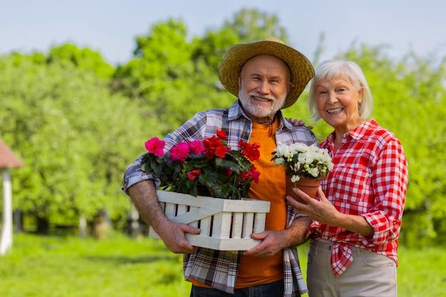 Coppia allegra. marito e moglie invecchiati allegri che sorridono ampiamente in piedi con vasi di fiori