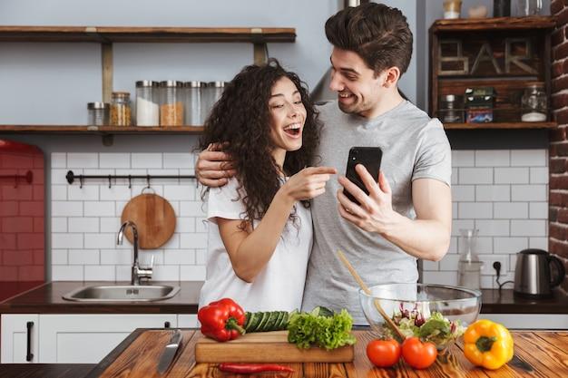 Coppia allegra che cucina una sana insalata fresca in cucina, si diverte, usa il cellulare