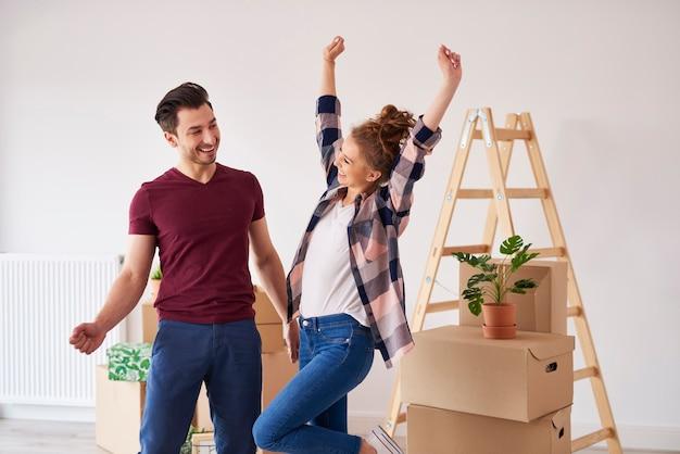 Coppia allegra che si diverte nel loro nuovo appartamento