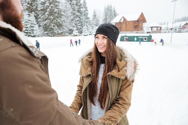 Coppia allegra che si tiene per mano e si guarda l'un l'altro all'aperto con la neve sullo sfondo
