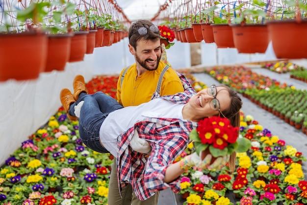 Coppie allegre nell'amore divertendosi alla serra. uomo che porta la donna mentre la donna tiene la pentola con i fiori. coppia in amore