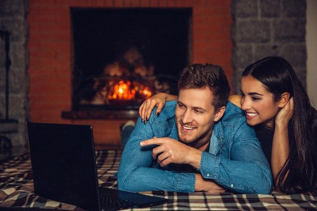 Coppie allegre che si trovano insieme sul pavimento e sulla risata. indica sullo schermo del laptop. le persone trascorrono del tempo al camino.