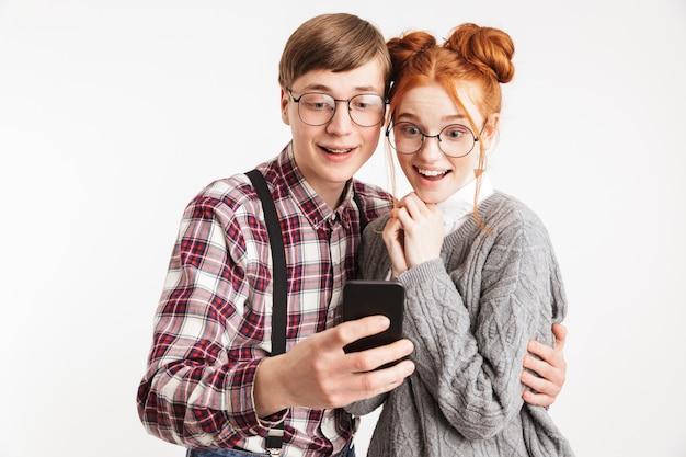Allegro paio di nerd della scuola che prendono selfie con il telefono cellulare isolato sopra il muro bianco