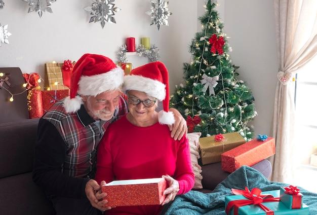 Allegra coppia di anziani seduti sul divano con cappelli di babbo natale che aprono un regalo con albero di natale e regali per la famiglia sullo sfondo. amore e concetto di famiglia
