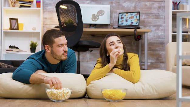 Coppia allegra che guarda la tv seduta sui cuscini per terra mangiando patatine e popcorn con il loro gatto sullo sfondo.