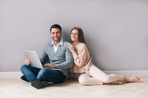 Coppie allegre con il computer portatile sul pavimento a casa. acquisti online.