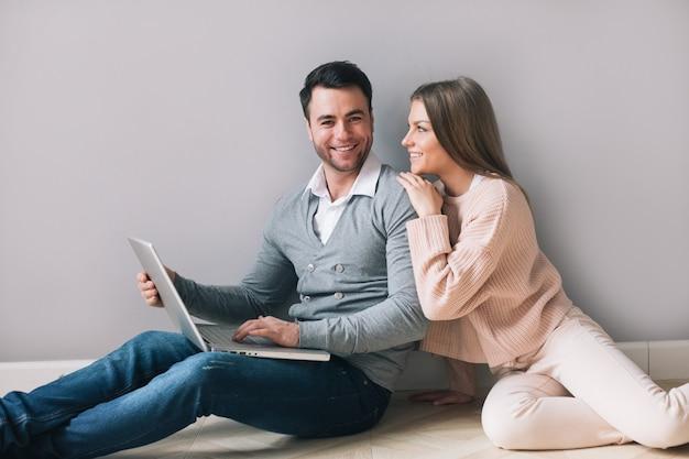 Coppie allegre con il computer portatile a casa. acquisti online.