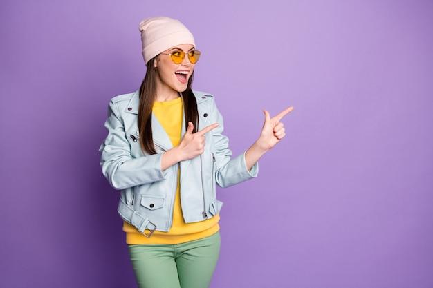 Allegra ragazza pazza promotore punto dito indice copyspace indicare annunci promo sconto consigliare scelta decisione consiglio indossare pantaloni gialli verdi isolati colore viola sfondo