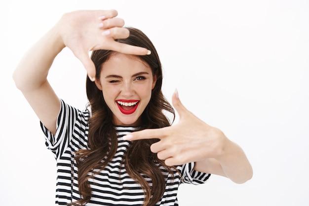 Allegra giovane donna creativa che fa cornici per le dita, guarda attraverso e strizza l'occhio con gioia, traendo ispirazione fotografando