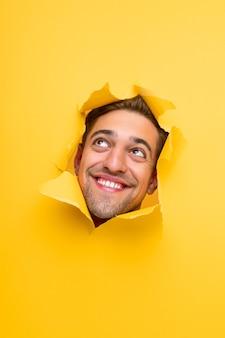 Allegro curioso giovane maschio barbuto che sbircia dal buco in carta gialla e alza lo sguardo