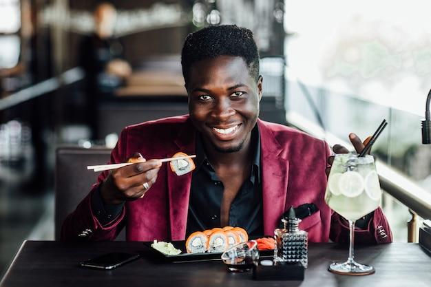 Ragazzo africano allegro capelli ricci che tiene i rotoli di sushi delle bacchette. terrazza del ristorante di pesce cibo cinese. mojito sul tavolo.