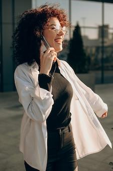 Allegro imprenditore caucasico dai capelli ricci sta parlando con qualcuno al telefono mentre posa felicemente fuori
