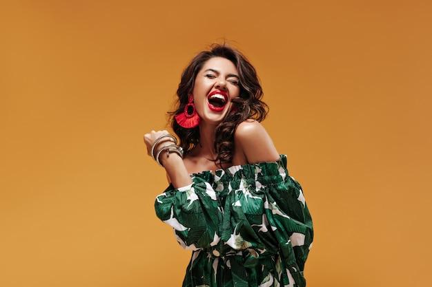 Donna riccia allegra con rossetto rosso e orecchini moderni in prendisole verde fresco che ride e posa con gli occhi chiusi sul muro isolato
